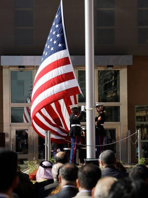 People watch the U.S. flag as it is raised during a ceremony marking the opening of the new U.S. Embassy in Baghdad, Iraq, Monday, Jan. 5, 2009.