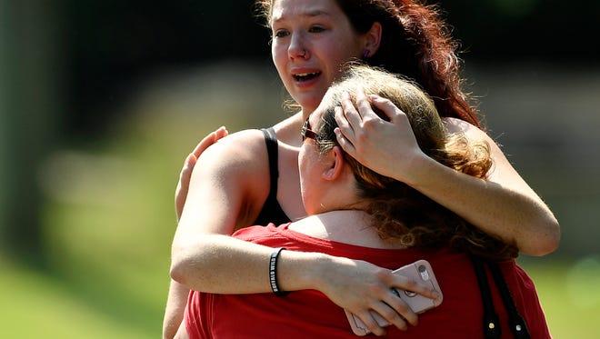 Kaitlyn Adams, rear, hugs Bridget Crow Polson, front, sister of victim Melanie Crow Smith, after a shooting at Burnette Chapel Church of Christ in Antioch, Tenn., Sunday, Sept. 24, 2017.