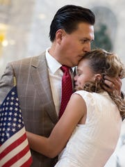 Victor Avalos, of Mexico, hugs daughter Isabelle after Avalos became a citizen during a naturalization ceremony at the state Capitol in Salt Lake City on Wednesday, July 19, 2017.