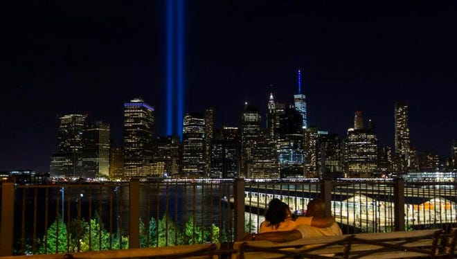 A couple watch the blue beams of the Tribute of Light piercing the air near the National September 11 Memorial and Museum in Manhattan from a park bench in Brooklyn on Sunday, Sept. 11, 2016. Sunday marked the 15th anniversary of the attacks.
