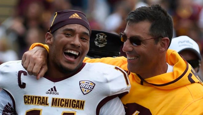 Central Michigan running back Thomas Rawls and head coach Dan Enos celebrate after the Chippewas won, 38-17, at Purdue on Sept. 6, 2014.