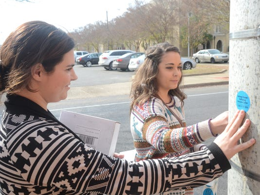 ANI Human Trafficking Louisiana College students junior Claire Lemoine (left) and sophomore Sarah Caskey, both members of Cats Against Trafficking Club post stickers in downtown Alexandria as they conduct a Human Trafficking Awareness campaign Wednesday, D