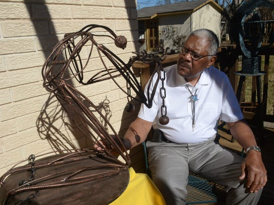 Morris Taft Thomas sits by a metal sculpture he fashioned to represent a slave on his knees with head and neck bowed and hands bound in chains.
