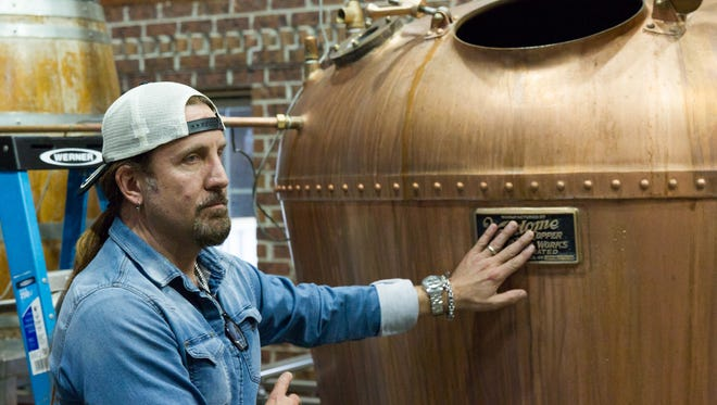 "Jesse James Dupree, the singer of the hard rock band Jackyl, gestures at a copper still the Full Throttle distillery in Trimble, Tenn., on Thursday, March 26, 2015. Dupree's plans to build his own distillery next door to Full Throttle are on hold because he doesn't want to have to conform to a state law setting a legal definition for which spirits can be marketed as ""Tennessee Whiskey."" (AP Photo/Erik Schelzig)"