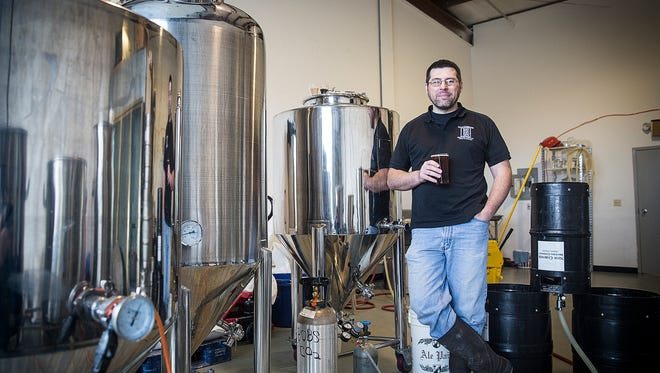 Sean Brady holds a glass of beer next to fermenting tanks at New Corner Brewing Co. in Muncie.