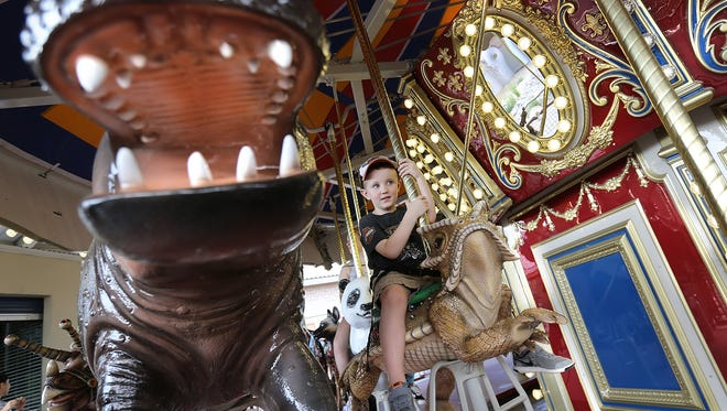 Henry Leivas, 5, enjoys a ride on the new endangered species carousel at the El Paso Zoo Thursday.