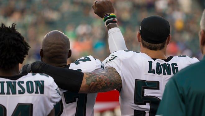 Malcolm Jenkins (left) holds his fist in the air while teammate Chris Long puts his arm around him during a recent game. Jenkins has raised his fist to protest social injustices.