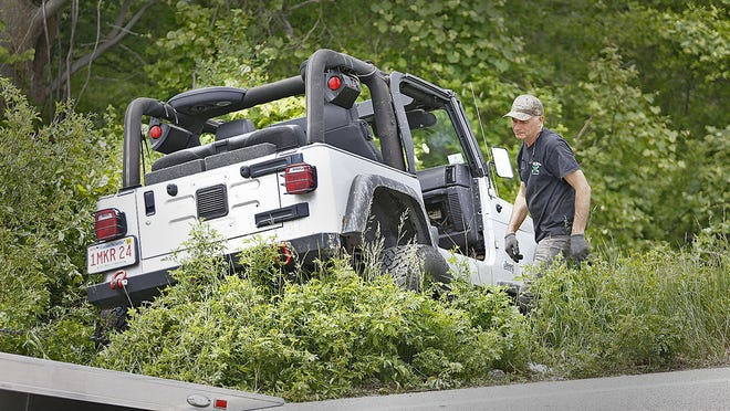A tow truck driver recovers a Jeep from the woods off Hatherly Road, Scituate which injured two passengers on Thursday, June 11.