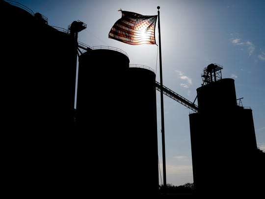 A flag flies over the Heartland Co-op grain elevator, Thursday, April 5, 2018, in Dallas Center, Iowa. The trade dispute with China is threatening to rattle small-town economies and election-year politics. Just seven months before the 2018 midterm elections, Trump's faceoff with China over trade has exposed an unexpected political vulnerability in what was supposed to be the Republican Party's strongest region: rural America.