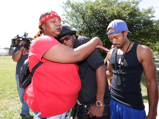 Patrick Smith (second right), the father of the man killed by police, and Sha Stinson, the aunt of the man, console one another near the burnt gas station at N. Sherman Blvd. and W. Burleigh St.