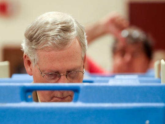 A voter in the background gives a thumbs-down sign as Senator Mitch McConnell fills out his ballot at Bellarmine University on Tuesday. November 4, 2014