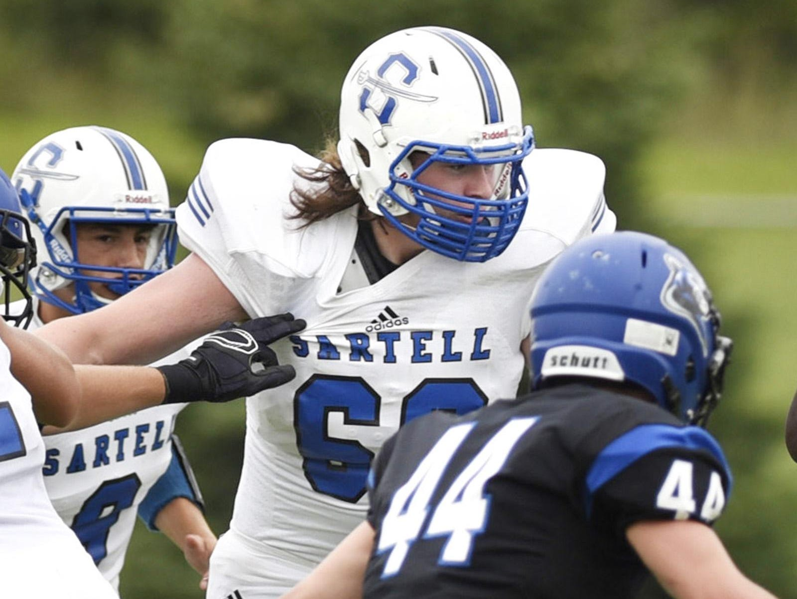 Sartell offensive lineman Ben Gault blocks for a runner against Rogers during the first half on Aug. 12 in Rogers.