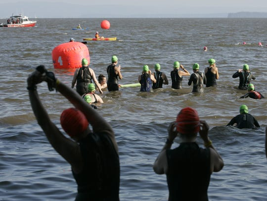 Participants swim in the Hudson River during action