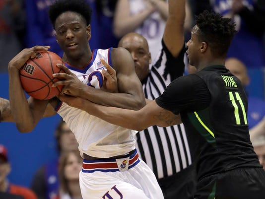 Kansas guard Marcus Garrett (0) controls the ball while covered by Baylor forward Mark Vital (11) during the second half of an NCAA college basketball game in Lawrence, Kan., Saturday, Jan. 20, 2018. (AP Photo/Orlin Wagner)