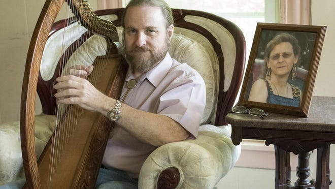 Guy Lattimore taught himself to play a medieval harp as part of the grieving process after the death of his wife, Kathy Lattimore, on Dec. 31, 2013.