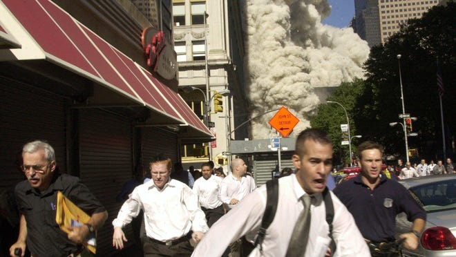 Stephen Cooper, who died March 28 in Palm Beach County from the coronavirus, achieved an element of fame on 9/11 when he was photographed, with envelope under arm at far left, fleeing the collapsing south tower of the World Trade Center.
