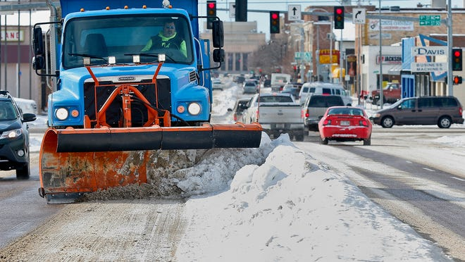 <137>Darren Yatsko, an equipment operator with the city of Great Falls, uses<137> A snow plow is used to rebunch snow berms on Central Avenue in March. Snow is in the forecast, with temperatures expected to climb back up to the mid-60s later this week.