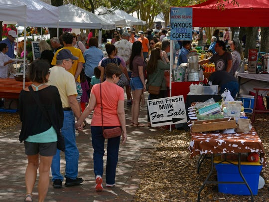 Visitors check out the vendor booths Saturday at the Palafox Market in downtown Pensacola.