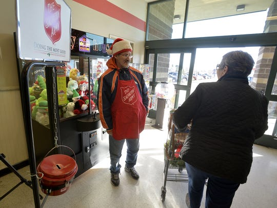 Salvation Army bell ringer Jimmy Melton wishes a shopper a merry christmas after her donation on Tuesday afternoon at Smith's grocery store.