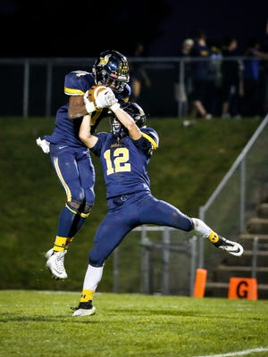 Wana Mwondela, left, and Nate Magnusson of Haslett converge for a first quarter interception against  Waverly Friday, October 7, 2016 at Haslett.
