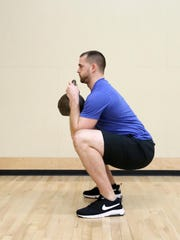 Kyle Davey, head trainer at Courthouse in South Salem, demonstrates a squat.