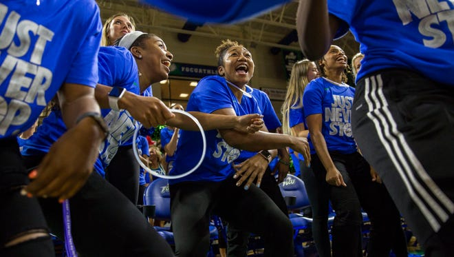 FGCU women's basketball team members Davion Wingate, left, Kerstie Phills, center, and Erica Nelson, right, celebrate after finding out they will be playing Missouri during the NCAA Tournament selection party in Alico Arena on Monday.