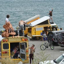 A woman dances on top of a van while other people set up camp on Blockhouse Beach at Pyramid Lake on Aug. 25, 2014, northeast of Reno, Nev. Thousands of Burning Man enthusiasts were on the outside looking in Monday after a rare batch of heavy rain forced organizers to temporarily close entry.