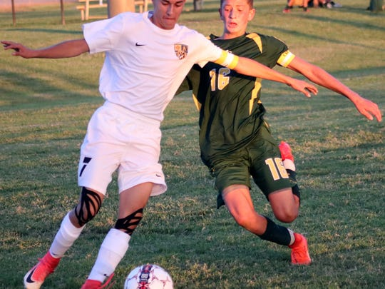Alamogordo's Keith Wilder, left, advances the ball up field while being pursued by a Mayfield defender.