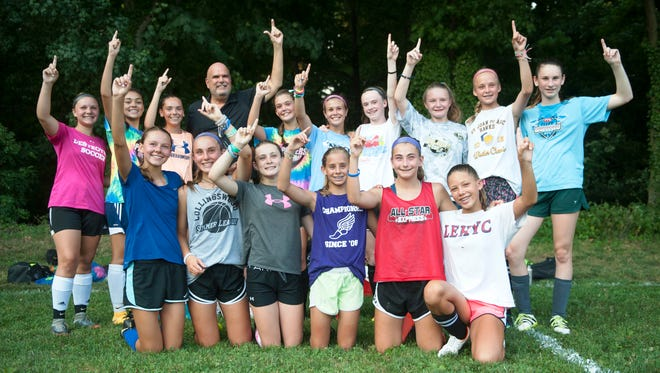 Members of the Haddonfield United U13 Girls Soccer Team pose for a photo with Haddonfield Mayor Neal Rochford, as Rochford visted the team as they practiced at Scout Field in Haddonfield on Monday, July 16, in preparation to compete in the National Cup tournament in Aurora, Colorado.