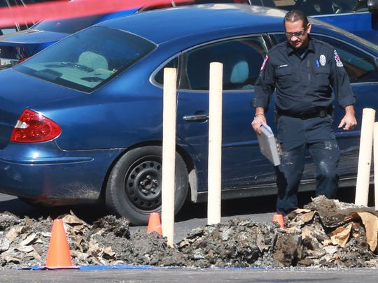 An El Paso Fire Department investigator examined burnt debris removed from an apartment in the Las Casitas Apartment complex Monday.