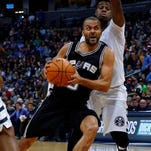 San Antonio Spurs guard Tony Parker (9), from France, is fouled by Denver Nuggets guard Emmanuel Mudiay (0) during the third quarter of an NBA basketball game Friday, Nov. 27, 2015, in Denver. (AP Photo/Jack Dempsey)