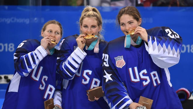 Kendall Coyne, Amanda Kessel and Nicole Hensley celebrate with their gold medals after defeating Canada.