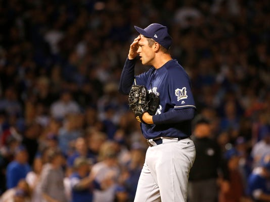 Milwaukee Brewers relief pitcher Jared Hughes wipes his face after delivering a wild pitch, scoring Chicago Cubs' Jon Jay, during the sixth inning of a baseball game Tuesday, April 18, 2017, in Chicago. (AP Photo/Charles Rex Arbogast)