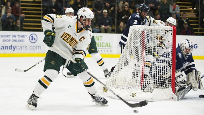 Catatmounts forward Mario Puskarich (21) looks to pass the puck in front of the net during the men's hockey game between the New Hampshire Wildcats and the Vermont Catamounts at Gutterson Field House on Friday night February 10, 2017 in Burlington. (BRIAN JENKINS/for the FREE PRESS)