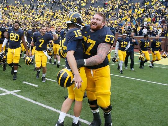 Kyle Kalis hugs quarterback Jake Rudock as they walk