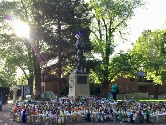 Bottles surround the statue of John Mackay at the University