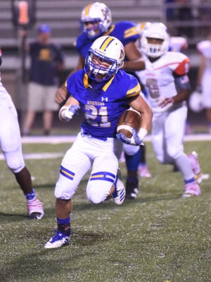 Mountain Home's Brad Litty carries against Marion last week at Bomber Stadium.