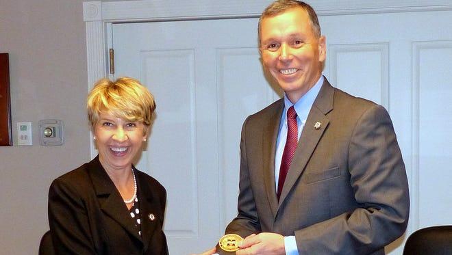 Mansfield University Trustees ChairBobbi Kilmer presents retiring President Fran Hendricks with the Mansfield University Presidential Coin for Excellence.