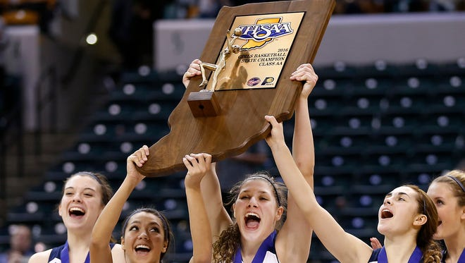 Central Catholic players Sarah Scheetz, from left, Jenni Harkcom, Cameron Onken and Emma Gerrety hoist the Class 2A trophy after defeating Covenant Christian 56-43 in the Class 2A State Finals Saturday, February 27, 2016, at Bankers Life Fieldhouse in Indianapolis.