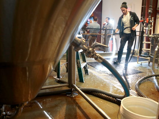 Brewer Rick Schawe with MadTree Brewing sprays down the brewery floor on Thursday.