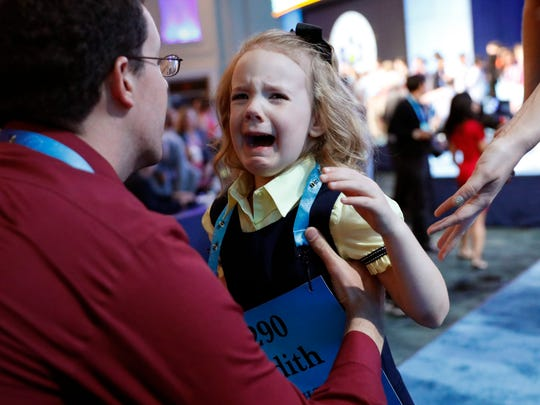 Justin Fuller picks up his daughter Edith Fuller, 6, from Tulsa, Okla., as she cries after she didn't make the Thursday finals of the 90th Scripps National Spelling Bee