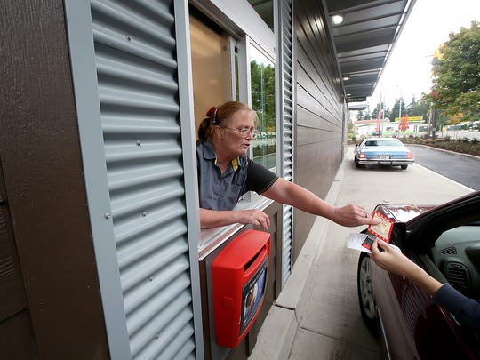 Kathy Silverman works the drive-thru window for the grand re-opening of the McDonald's on Mile Hill in Port Orchard.