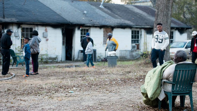 Louis Vason, 64, sits in his neighbors yard in front of his house on John Morris Avenue that was damaged by a Saturday blaze as Montgomery Fire Department officials investigate.