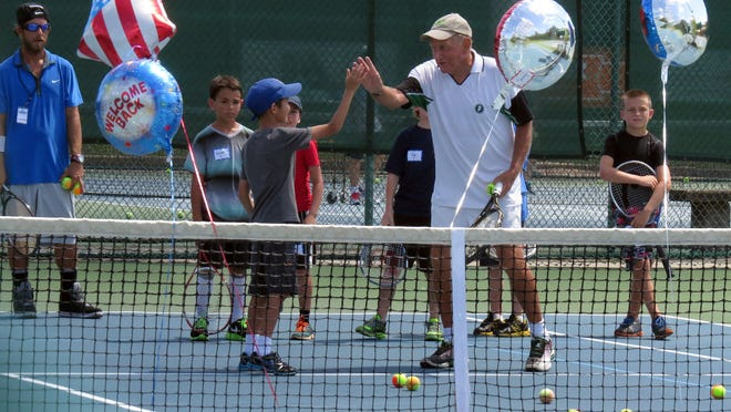 Volunteer instructor Bill Kellenberger high-fives one of the players participating in the Racquet Roundup on Thursday at the Roger Scott Tennis Center.