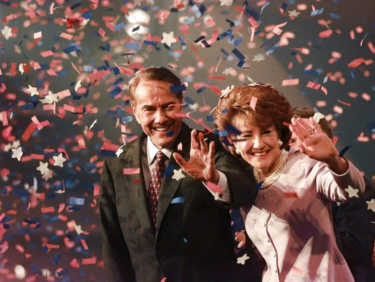 Bob Dole and his wife, Elizabeth, wave from the podium