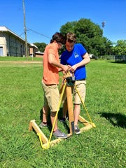 Carl Willis and Caleb Rhodes stretch a resistance band to prepare their slingshot for launch Wednesday.