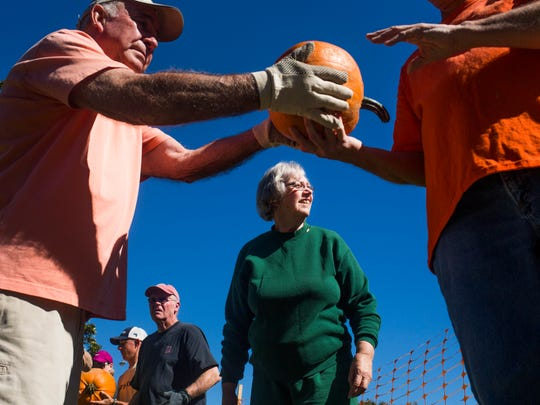 Phyllis Morrison, center, helps unload pumpkins at Trinity United Methodist Church on Wednesday, October 12, 2016 in Anderson.