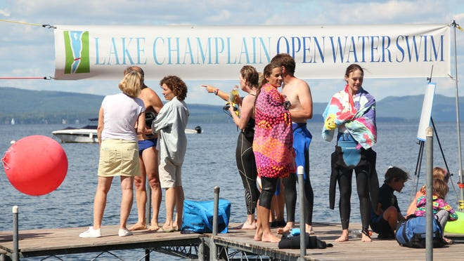 Volunteers and family members wait on the dock of Charlotte's public beach for open water race swimmers to reach the end on Sunday.