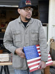 Iraq War veteran Rolando Corral holds the first wooden flag he ever made close. The flag is like a security blanket for the veteran, he said.