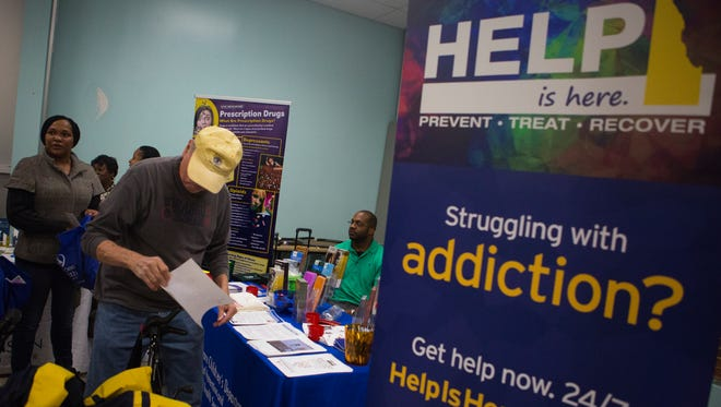 Attendees at the Imagine Delaware What Heroin Costs Delaware resource fair visit informational booths throughout the John Dickinson High School cafeteria Monday night.